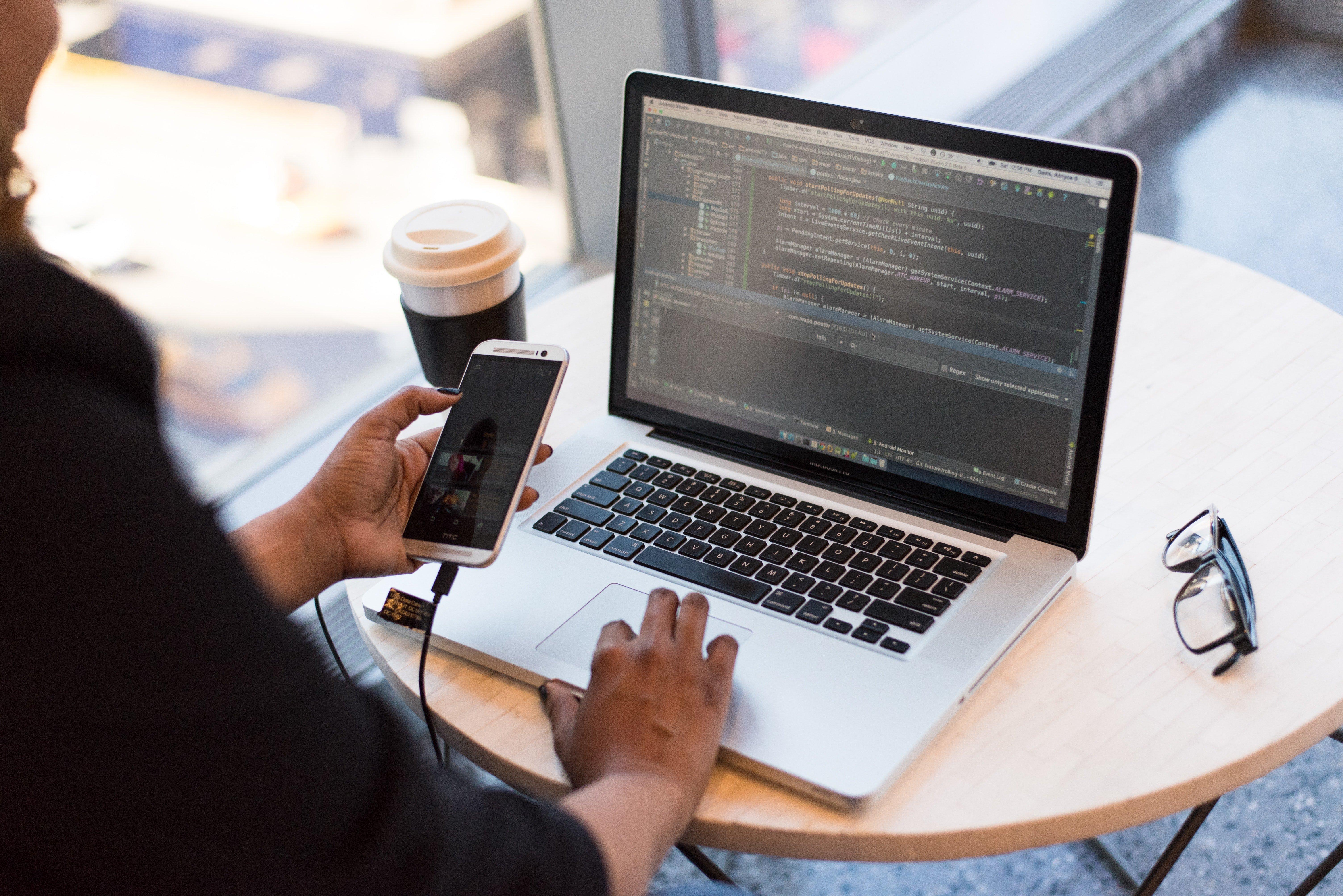 برمجة مواقع الويب person looking at phone and at macbook pro 1181244